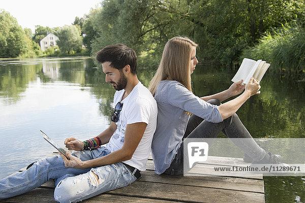 Junges Paar am Steg am See mit Buch und Tablette