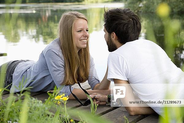 Lächelndes junges Paar auf einem Steg am See liegend