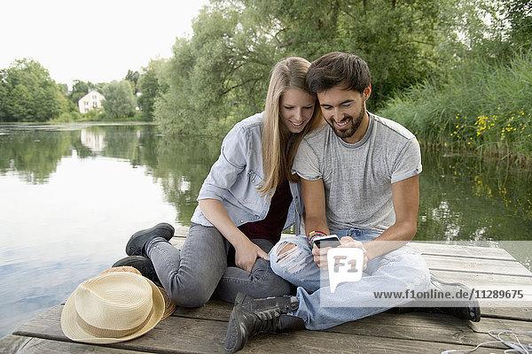Lächelndes junges Paar am Steg eines Sees mit Handy