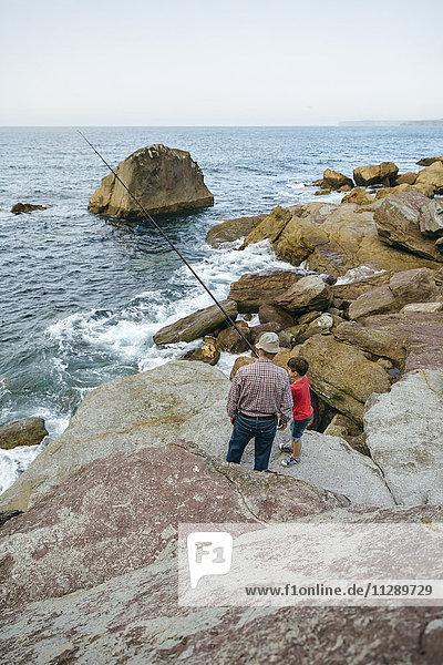 Großvater und Enkel beim gemeinsamen Fischen am Meer