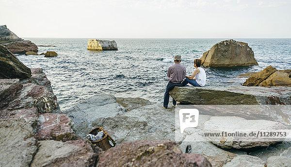 Seniorenpaar beim Fischen am Meer auf Felsen sitzend