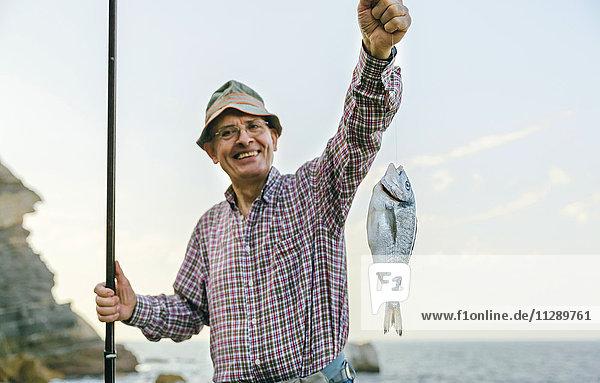 Fröhlicher älterer Mann mit Fisch an der Angelschnur, Fröhlicher älterer Mann mit Fisch an der Angelschnur