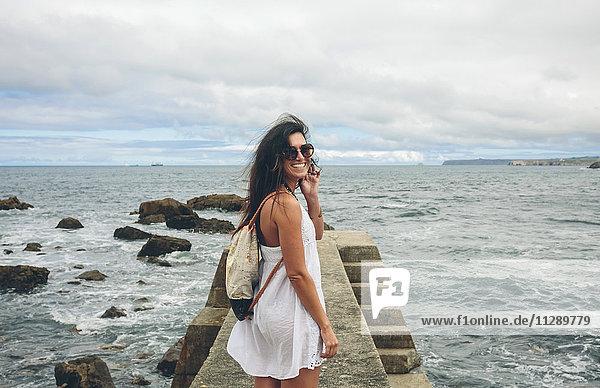 Lächelnde Frau mit Sonnenbrille und Rucksack am Pier stehend