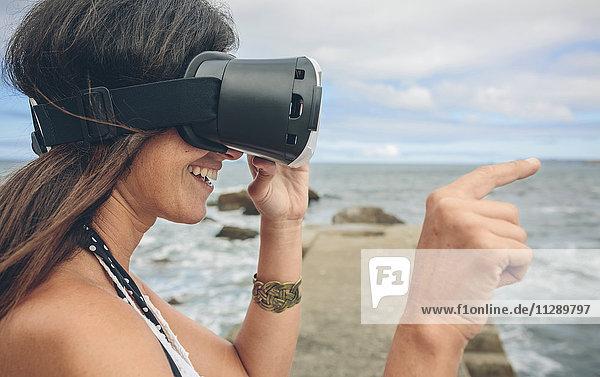 Lächelnde Frau mit Virtual Reality Brille im Freien
