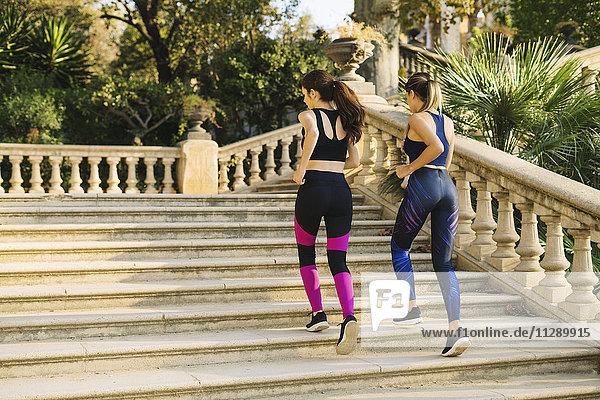 Zwei junge Frauen joggen auf der Treppe im Park