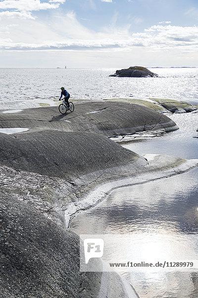 Person cycling at sea