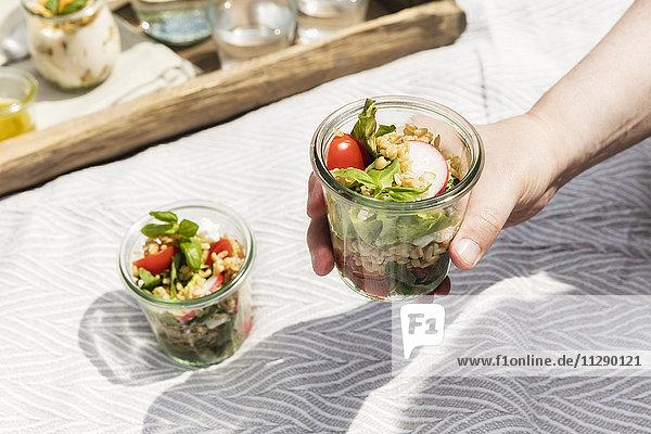 Person im Glas mit vegetarischem Hafersalat