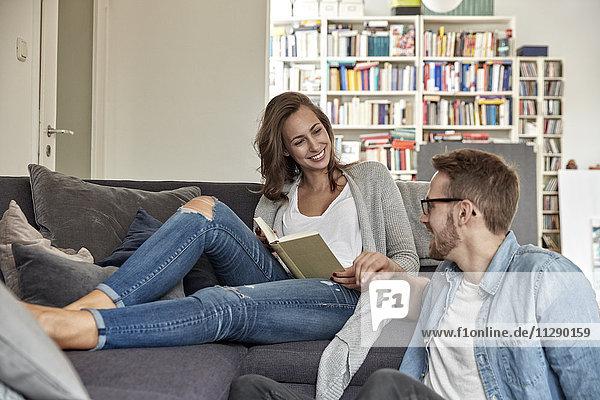 Lächelndes Paar entspannt sich gemeinsam im Wohnzimmer