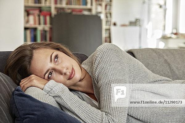 Porträt einer jungen Frau  die sich auf der Couch im Wohnzimmer entspannt.