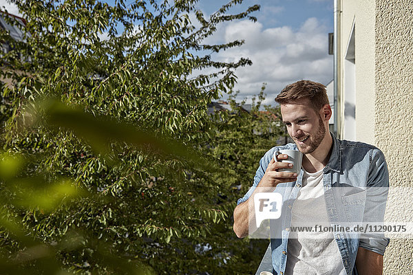 Smiling man drinking coffee on balcony