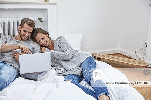 Lächelndes Paar auf Bettzeug auf dem Boden liegend mit Blick auf Laptop