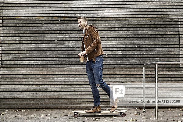 Lächelnder Mann mit Kaffee zum Skateboarden vor der Holzwand