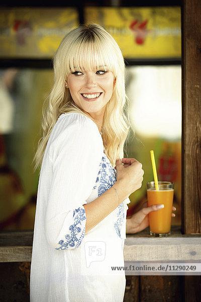 Porträt einer lächelnden blonden Frau mit Getränk vor einer Strandhütte
