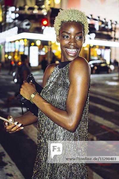 USA  New York City  Porträt der glücklichen jungen Frau am Times Square bei Nacht