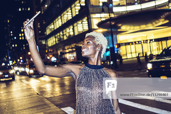 USA  New York City  smiling young woman on Times Square at night taking selfie