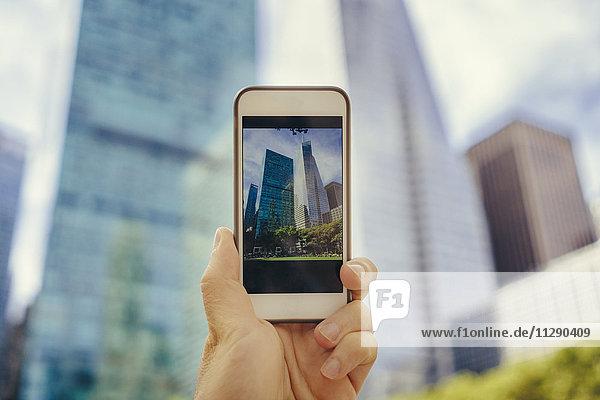 Mann fotografiert mit Handy in Manhattan