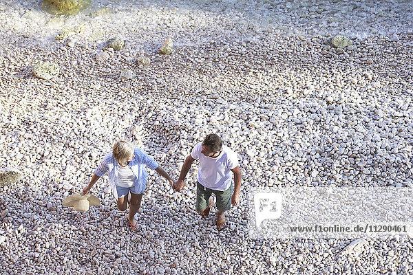 Draufsicht eines älteren Paares  das am Strand spazieren geht.