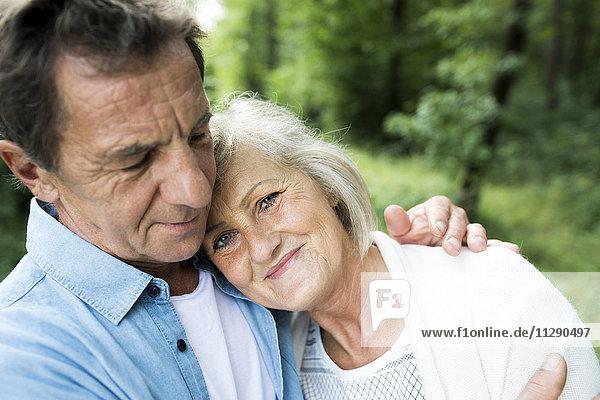 Porträt einer lächelnden Seniorin mit dem Kopf auf der Schulter ihres Mannes im Wald.