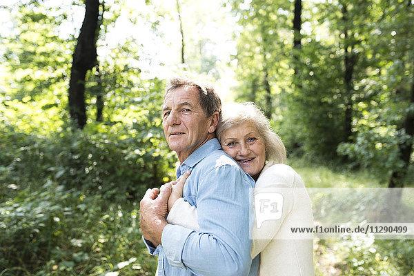 Porträt eines glücklichen Seniorenpaares beim gemeinsamen Entspannen im Wald
