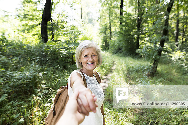 Portrait of happy senior woman holding man's hand in nature