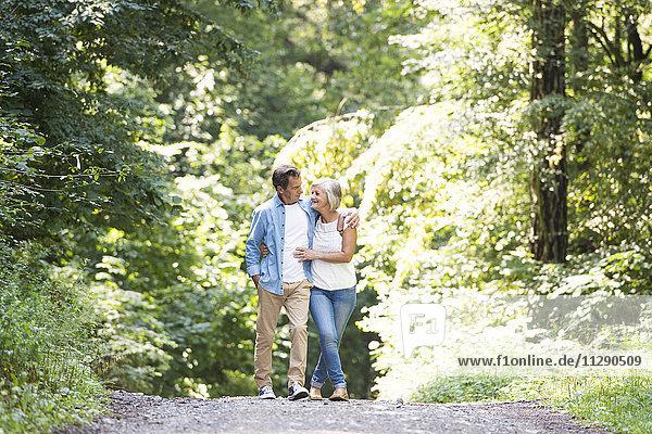 Glückliches älteres Paar  das Arm in Arm im Wald geht.