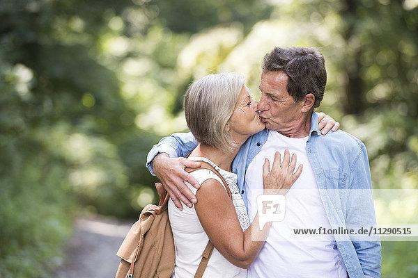 Seniorenpaar in der Natur küssen