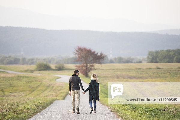 Junges Paar beim Wandern in ländlicher Landschaft