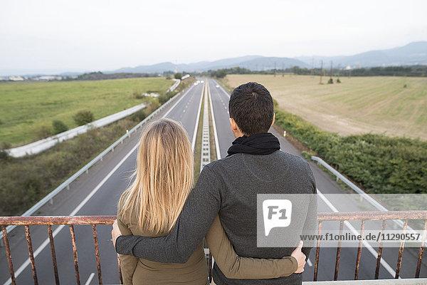 Paar auf der Brücke mit Blick auf die Autobahn