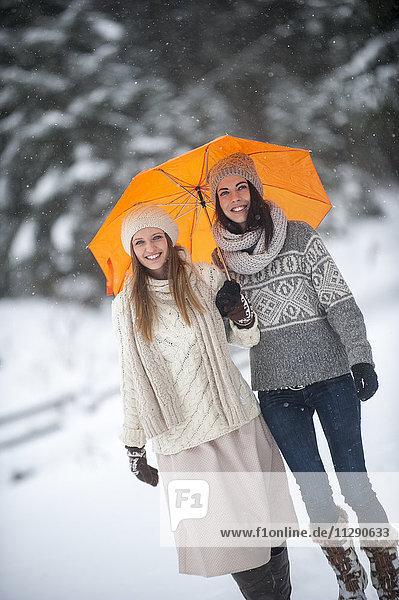 Porträt von zwei Freunden mit gelbem Regenschirm im Winter