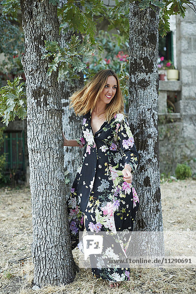 Smiling blond woman wearing dress with floral design
