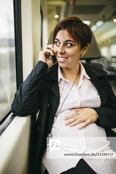 Schwangere Frau im Zug auf dem Handy
