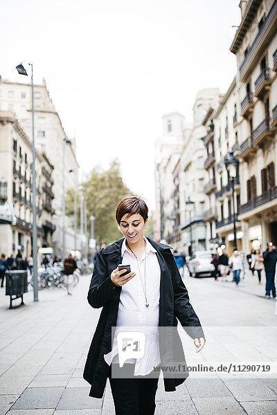 Schwangere Frau mit Handy zu Fuß in der Stadt