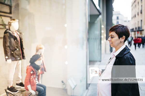 Schwangere Frau mit Handy im Schaufenster