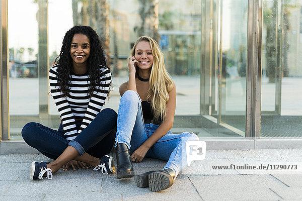 Zwei glückliche junge Frauen sitzen an der Glaswand im Freien.