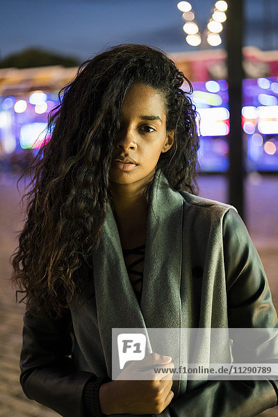 Portrait of a young woman on a funfair at night