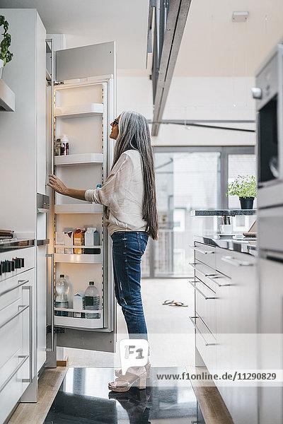 Frau in der Küche sucht im Kühlschrank
