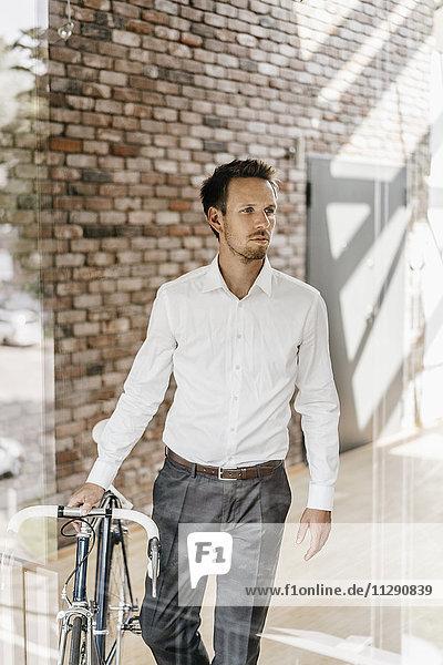 Geschäftsmann mit Fahrrad im Büro