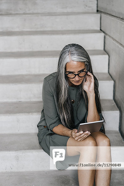 Woman with long grey hair sitting on stairs holding tablet