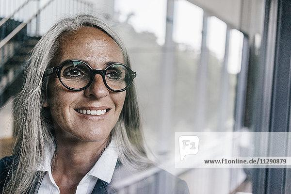 Lächelnde Geschäftsfrau mit Blick aus dem Fenster