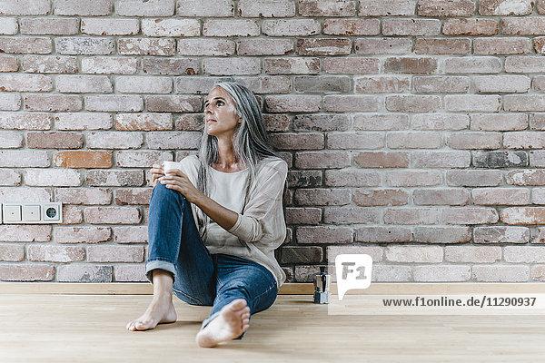 Frau mit langen grauen Haaren auf dem Boden an der Ziegelwand sitzend