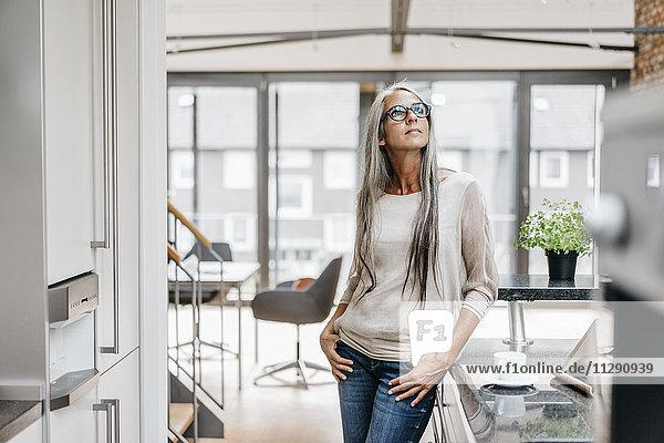 Frau mit langen grauen Haaren in der Küche nach oben schauend