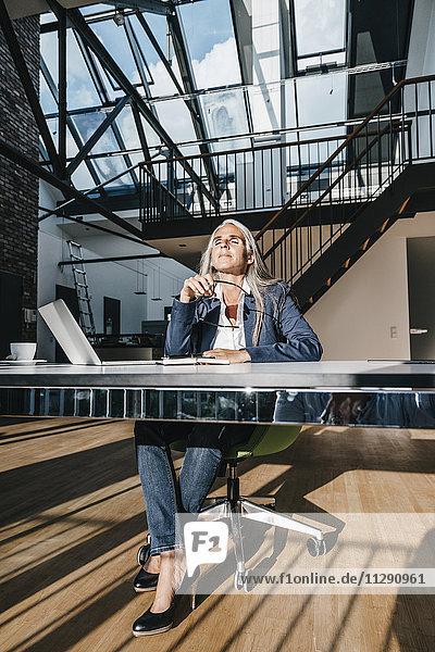 Geschäftsfrau am Schreibtisch genießt Sonnenlicht