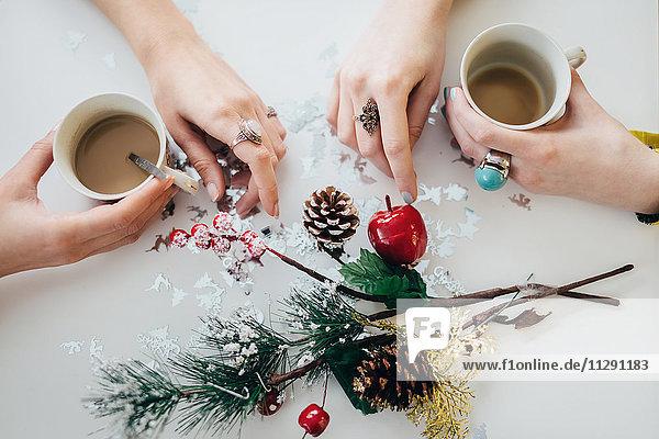 Hände von zwei Frauen halten Tassen Kaffee auf einer Tischplatte mit weihnachtlicher Dekoration.