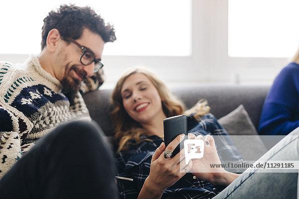 Junge Frau teilt Nachricht auf dem Smartphone mit Freund im Wohnzimmer