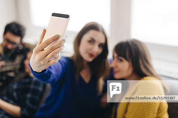 Junge Frau  die einen Selfie mit einem Smartphone nimmt