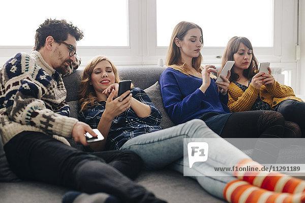 Vier Freunde mit Smartphones auf der Couch im Wohnzimmer hängen heraus