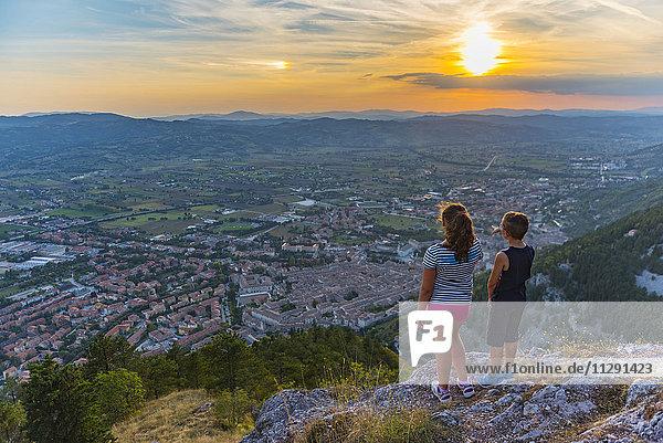 Italien  Gubbio  Rückansicht von zwei Kindern  die die Stadt von oben betrachten.