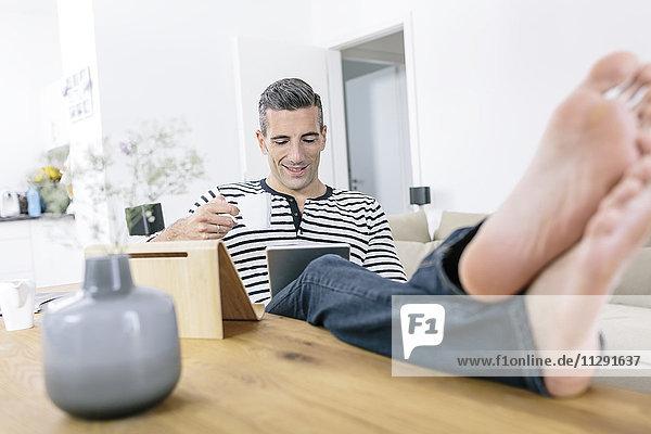 Entspannter Mann zu Hause mit Tablette