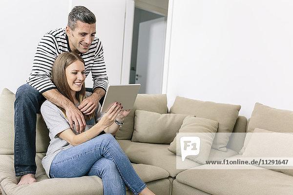 Lächelndes Paar zu Hause mit Tablette