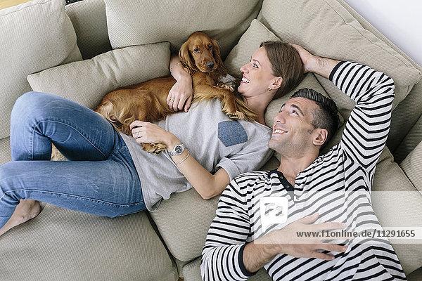 Lächelndes Paar mit Hund auf der Couch liegend